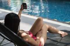 Woman selfie by smartphone at pool. Asian beautiful woman in red one piece swimsuit selfie or take her picture by smartphone at swimming pool. Attractive girl royalty free stock photo