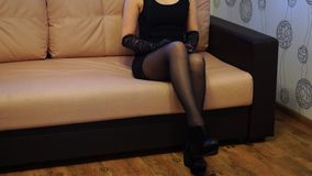 Woman in short black dress and stockings. Puts one leg on other stock footage