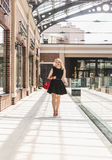 Sexy woman in short black dress walking at shopping mall Royalty Free Stock Photography