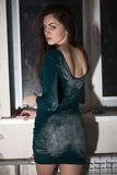 Sexy woman in short dress. Rear view of sexy woman in fashionable short dress looking over shoulder with window in background Stock Photos