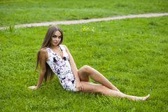 Sexy woman in short dress sitting on green grass Royalty Free Stock Photography