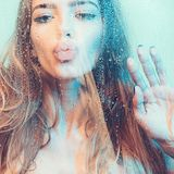 Sexy woman in shower. Attractive young naked woman under water drops on blue background stock photo
