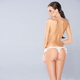 Sexy woman showing off her buttocks. Slender sexy woman showing off her shapely buttocks standing in a g-strap panty, facing away from the camera turning to look Stock Photography