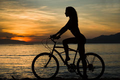 Sexy woman silhouette with bicycle with sunset and seat Stock Photo
