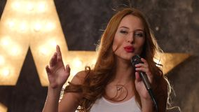 Sexy woman singer with microphone, shining star in stock footage