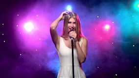 Woman singing into retro microphone, smoke effect. Slow motion. Blonde woman with long hair in white dress singing into a retro microphone and looks into the stock footage