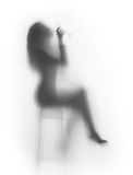 Sexy woman sits on chair, and drinks. Nice slim woman silhouette, who drinks Royalty Free Stock Photos
