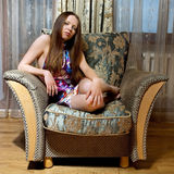 Sexy woman sitting on the armchair Royalty Free Stock Images