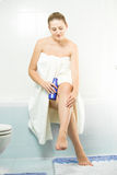 Sexy woman sitting in bathroom and applying lotion on legs Stock Photos
