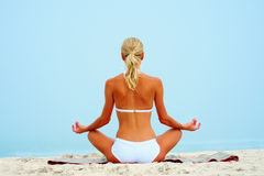 Sexy woman sitting on the beach and meditating Royalty Free Stock Images