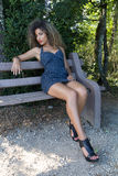 Sexy woman is sitting on a bench Royalty Free Stock Photos