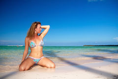 Sexy woman sitting on caribbean beach Royalty Free Stock Photo