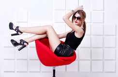 Sexy woman sitting on a chair. Fashion shot. Sexy woman in short black dress sitting on a chair. Fashion shot Royalty Free Stock Photo