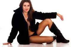 Sexy woman sitting in coat Stock Images