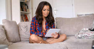 Sexy Woman Sitting on Couch with Tablet Computer Stock Photography