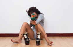 Sexy woman sitting on floor aims with toy gun Stock Photo