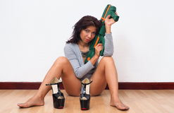 Sexy woman sitting on the floor holds toy gun. Sexy woman sitting on the floor wearing sexy rompers holds toy gun with black high heel shoes in front of her Stock Photography