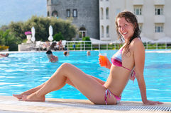 woman is sitting at poolside Stock Image