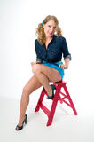 Sexy woman sitting on step ladder Royalty Free Stock Photography