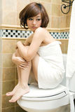 woman sitting on toilet royalty free stock image