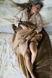 Sexy woman sleeping alone in bed. Partially covered with naked l stock photography