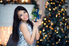 Sexy woman with a small Christmas present. Beautiful girl in a short dress sitting on the plaid on floor. Bright and. Joyful Christmas Royalty Free Stock Photography