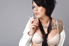 Sexy woman smoking a cigarette Royalty Free Stock Image