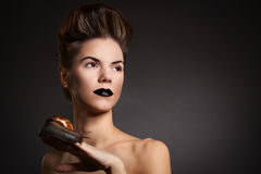 Woman with snail with black eyes and lips. Fashion. Gothic. Woman with snail with black eyes and lips in Gothic Halloween image royalty free stock photo