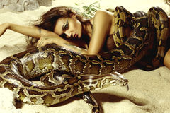 Sexy woman with a snake on the beach Royalty Free Stock Photography