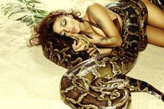 Sexy woman with a snake on the beach Stock Photo