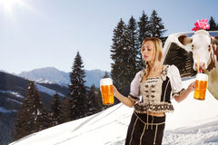 woman in snow and mountains serving beer Royalty Free Stock Images