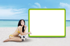 Sexy woman with a soccer ball and copyspace. Sexy woman wearing bikini posing with a soccer ball next to copyspace at the beach Stock Photography
