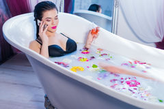 Sexy woman speaking on the phone while taking a bath Stock Image