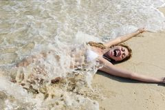Sexy woman splashed by wave on the beach Stock Image