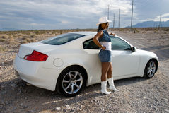 Sexy woman by sports car. African American woman wearing a short denim skirt and white cowboy boots and hat standing by a car, in the desert Stock Photo