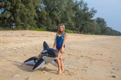 Woman in blue swimsuit on the beach with inflatable toy. Woman is standing on the beach in blue swimsuit with inflatable toy killer whale in her hands, Mai Khao stock photos