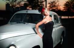 Sexy woman standing near car in retro style. Fashion portrait of beautiful sexy woman model girl posing standing near car in retro style with bright makeup at Royalty Free Stock Photo