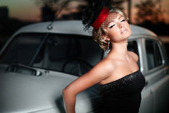 Sexy woman standing near car in retro style. Fashion portrait of beautiful sexy woman model girl posing standing near car in retro style with bright makeup at Royalty Free Stock Photos