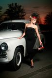 Sexy woman standing near car in retro style. Fashion portrait of beautiful sexy woman model girl posing standing near car in retro style with bright makeup at Stock Image