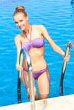 woman standing on pool ladder Stock Photo