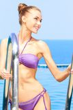Sexy woman standing on pool ladder Stock Photos