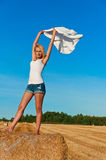 Sexy woman standing and posing on a wheat bale in a field Stock Images