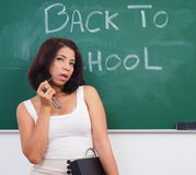 woman stands in front of chalkboard stock image