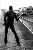 Sexy Woman Sticking Thumb Out for Ride. Black and White image of a woman at the railroad tracks trying to hitch a ride Stock Image