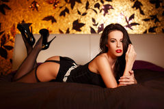 Sexy woman in stockings laying on bed Stock Photos