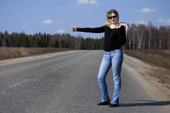 Sexy woman stopping car. Girl hitchhiking on the road Royalty Free Stock Image