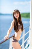 Sexy woman in stylish swimsuit standing on the aft of a sailing Royalty Free Stock Image