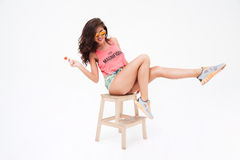 woman in sunglasses and candy posing on the chair Stock Image