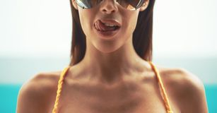 Sexy woman in sunglasses licking lips