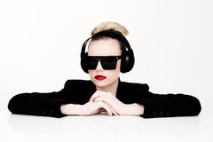 Sexy woman in sunglasses listening to music. Dramatic portrait of a sexy woman in sunglasses listening to music on a set of headphones leaning on a table looking Stock Photo